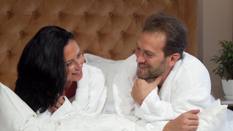 Reifes verheiratetes Paar bei der Bademantelunterhaltung, zusammen liegend im Bett im Hotel stockbilder