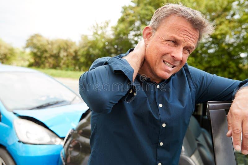 Reifung eines männlichen Motormanns mit Whiplash-Verletzung bei Autounfall, der aus dem Fahrzeug herauskommt lizenzfreie stockbilder