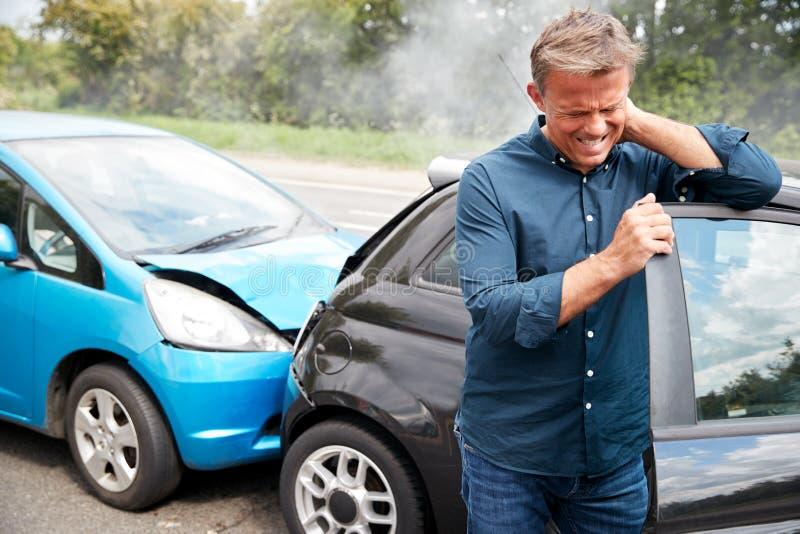 Reifung eines männlichen Motormanns mit Whiplash-Verletzung bei Autounfall, der aus dem Fahrzeug herauskommt stockbilder