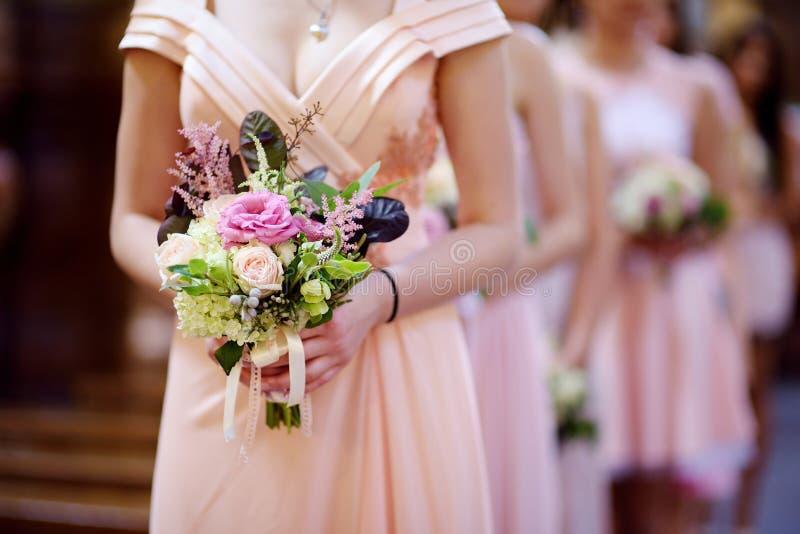 Reihe der Brautjunfern mit Blumensträußen an der Hochzeit lizenzfreies stockbild