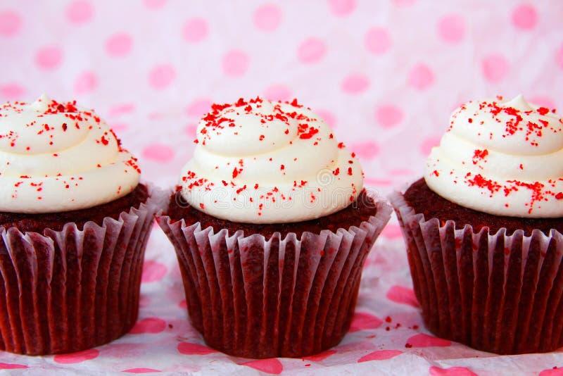 Reihe der roten Samtkleiner kuchen mit Rot spritzt stockbilder