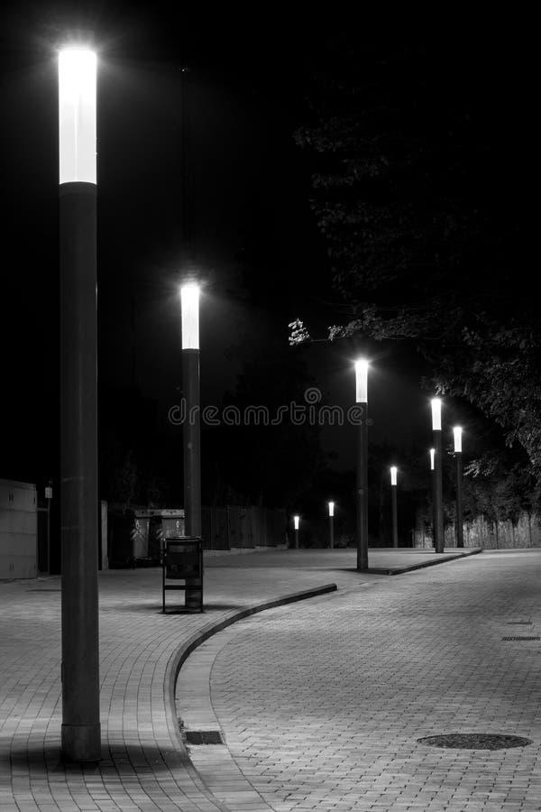 Reihe der Straßenbeleuchtung in gekurvt und in einer Pflasterstraße lizenzfreie stockbilder