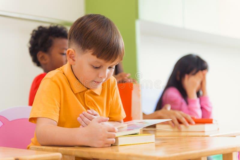 Reihe des multiethnischen grundlegenden Studentenlesebuches im Klassenzimmer Weinleseeffekt-Artbilder lizenzfreies stockfoto