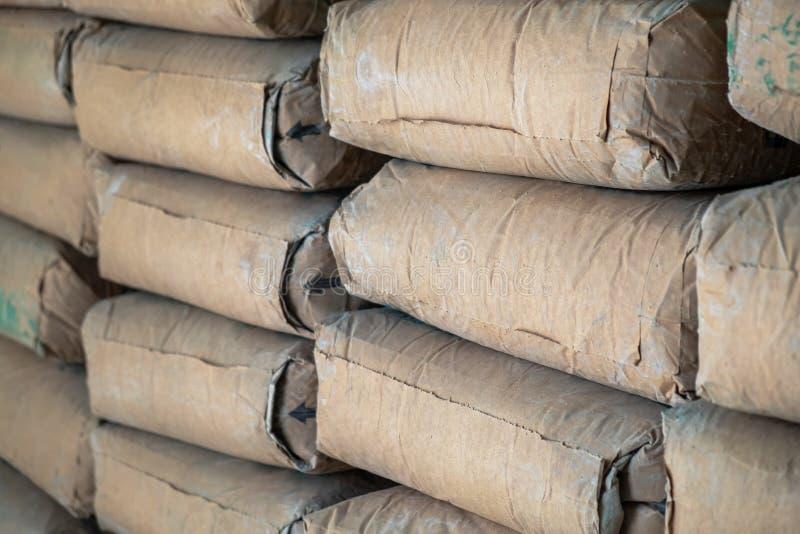 Reihe des rohen Brown-Zementsack-Lage-Stapels im Bauarbeit-Standort stockbilder