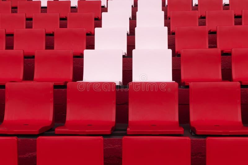 Reihe des rosa wei?en Stuhls unter Rot im Fu?ball- oder Fu?ballstadionssporthintergrund stockbild