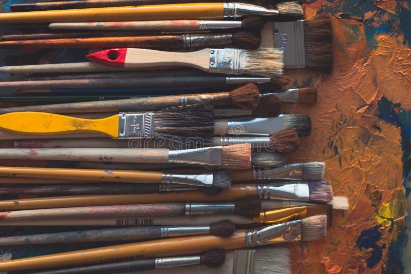 Reihe hölzerne verschiedene Größenmalerpinsel, die auf Palette mit alter Ölfarbe liegen, knackte Beschaffenheit im Kunststudio, D stockbild