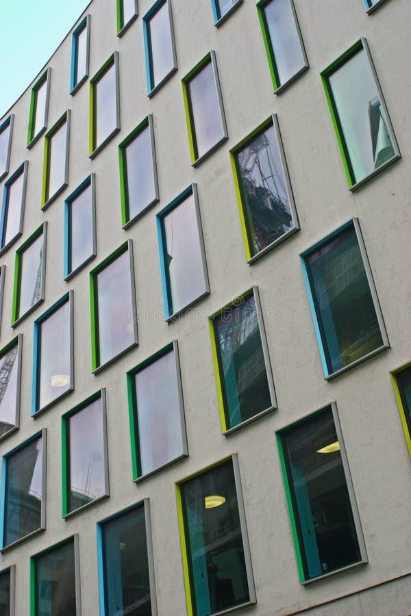 Reihe rechteckige Fenster mit bunten Rahmen in Gelbem, in Grünem, in Cyan-blauem und in Blauem auf grauer moderner Fassade von Vi stockfotografie