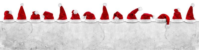Reihe roten weißen Weihnachtsmann-Weihnachtsweihnachtshutes auf leerem concret lizenzfreies stockbild