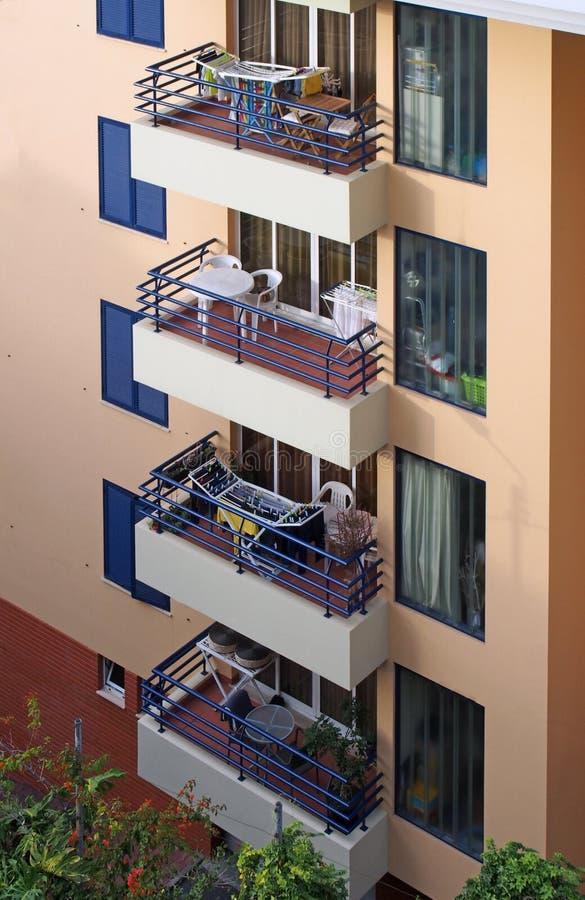 Reihe von Balkonen mit Tabellen und von Stühlen in einem orange und blauen konkreten Wohngebäude stockbilder