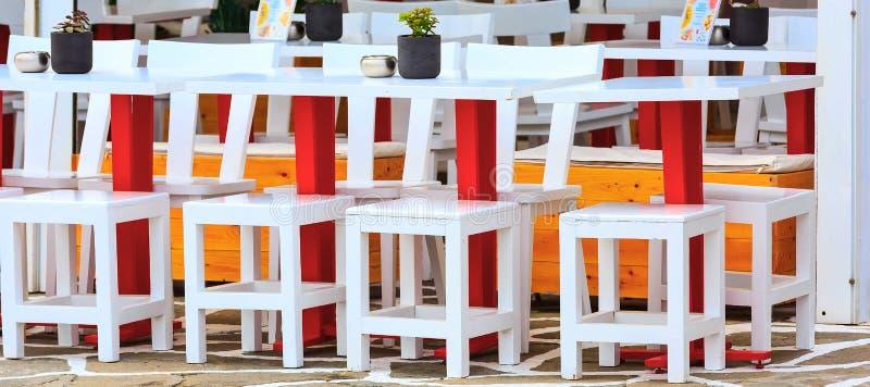 Reihe von bunten Tabellen und von Stühlen Café im im Freien lizenzfreies stockbild