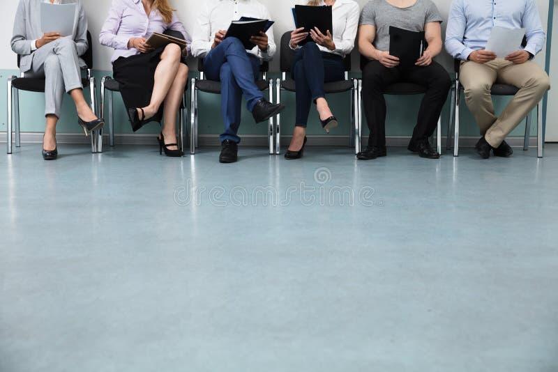 Reihe von den Kandidaten, die auf Stuhl sitzen stockbild