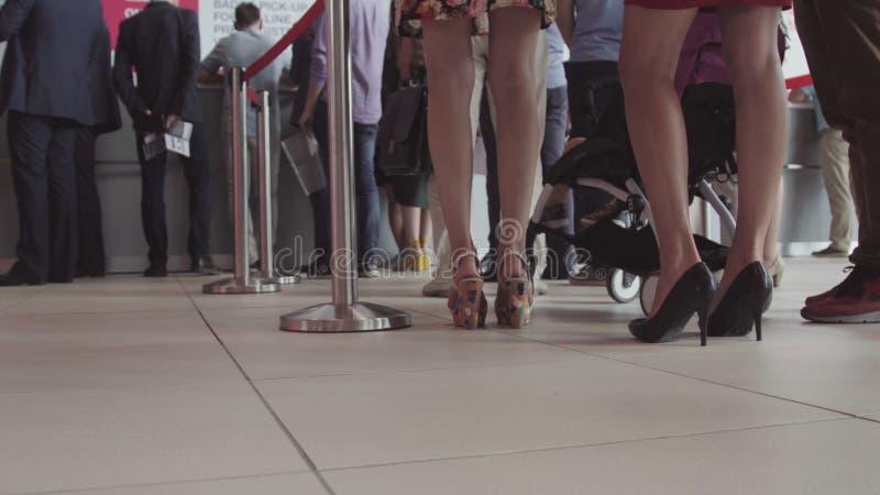 Reihe von den Leuten, die in einen Flughafen warten Füße Leute in der Linie am Flughafen stockfotografie