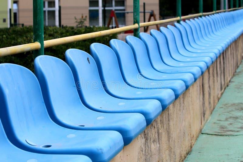 Reihe von den neuen blauen Plastiksitzen angebracht auf konkrete Zuschauertribünen mit Metallzaun und Gartenvegetation in Hinterg lizenzfreie stockbilder