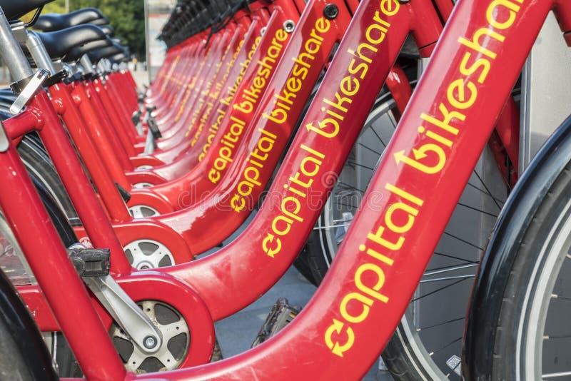 Reihe von den roten Fahrrädern benutzt im Haupt-Bikeshare-Programm, das auf dem Bürgersteig #3 stillsteht stockbilder