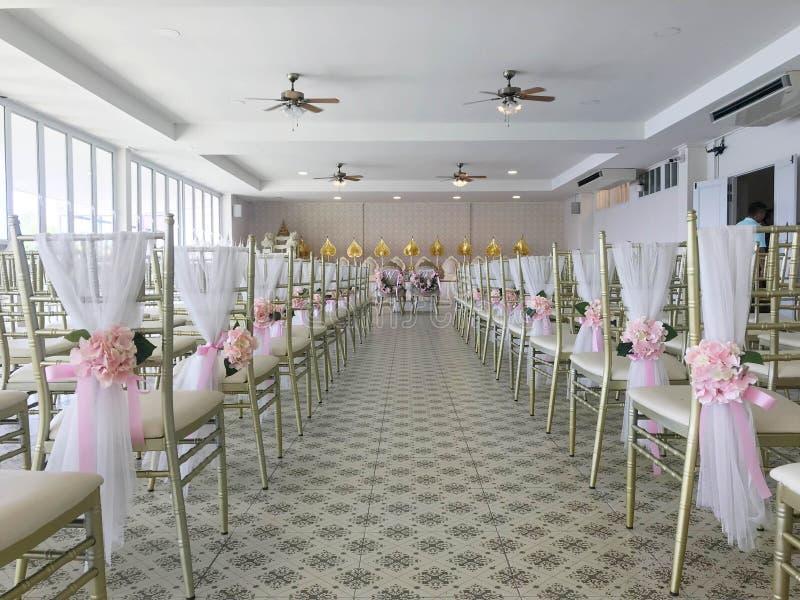 Reihe von den weißen Stühlen verziert mit Blume in der Hochzeitszeremonie lizenzfreie stockbilder