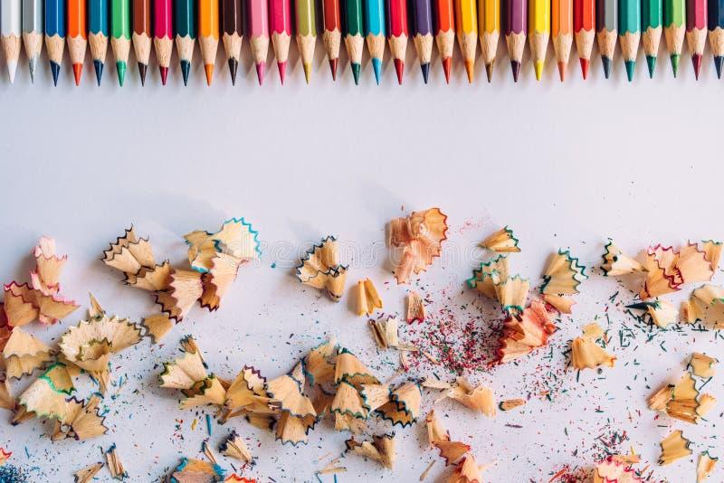 Reihe von farbigen Bleistiften und von Bleistiftrasuren auf einem Papier lizenzfreie stockbilder
