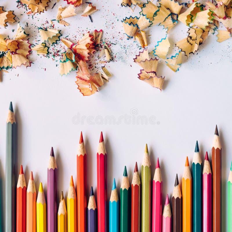 Reihe von farbigen Bleistiften und von Bleistiftrasuren auf einem Papier stockfotos