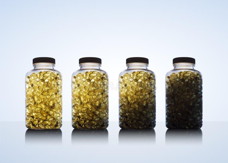 Reihe von Flaschen voll des Fischöls Omega 3 und des Vitamins D stockfotografie