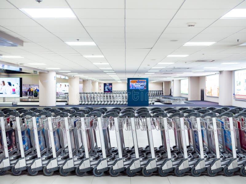 Reihe von Flughafengepäckwagen im Flughafenabfertigungsgebäude stockbild