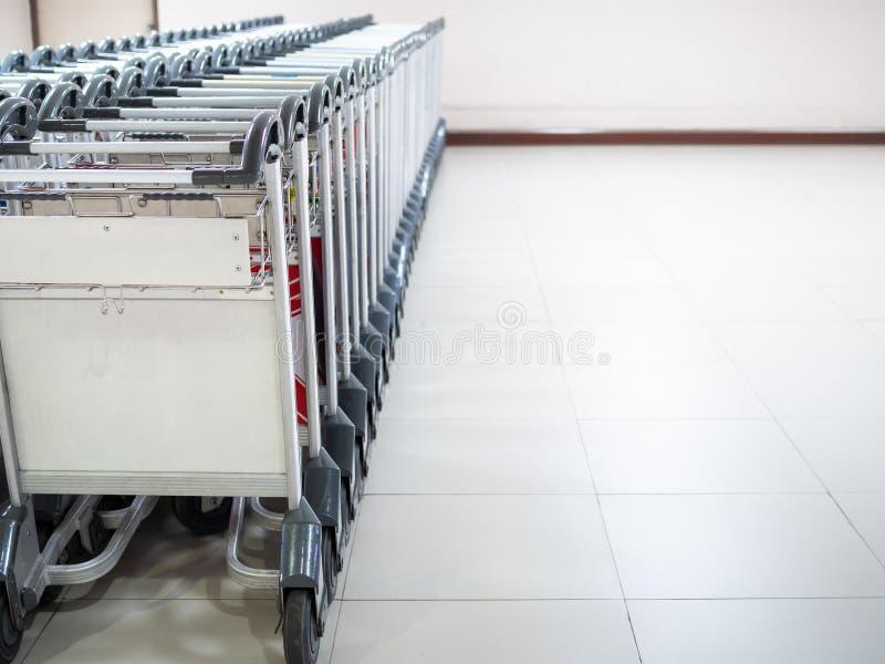 Reihe von Flughafengepäckwagen im Flughafenabfertigungsgebäude stockfotografie