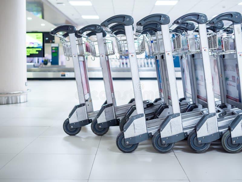 Reihe von Flughafengepäckwagen im Flughafenabfertigungsgebäude stockbilder
