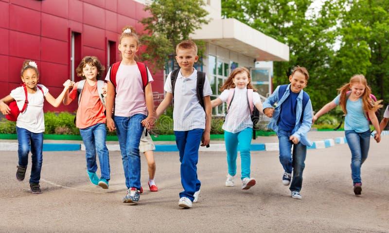 Reihe von glücklichen Kindern mit Taschen nähern sich Schulgebäude stockbilder