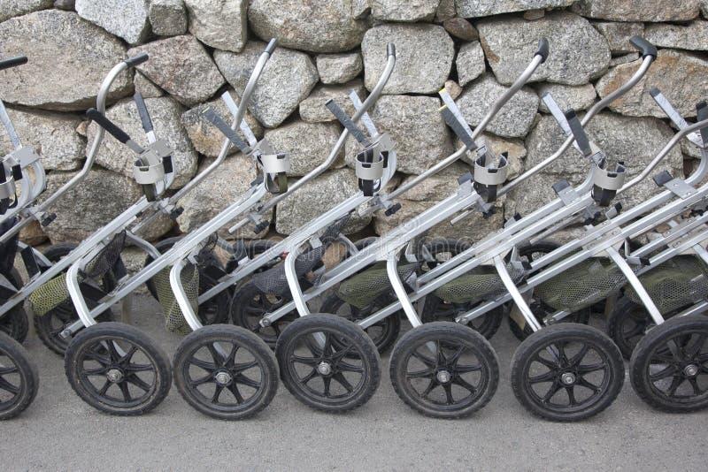 Reihe von Golfzugwagen stockfotos