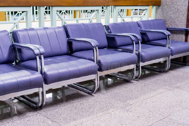 Reihe von hellpurpurnen Stühlen in der Krankenhaushalle lizenzfreie stockbilder
