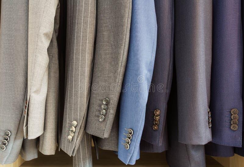Reihe von Mannanzugsjacken auf Aufhängern lizenzfreies stockbild