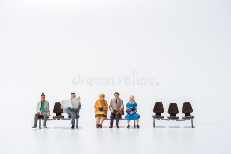 Reihe von Miniaturleuten stellen das Sitzen auf Bankweißhintergrund dar lizenzfreie stockfotos