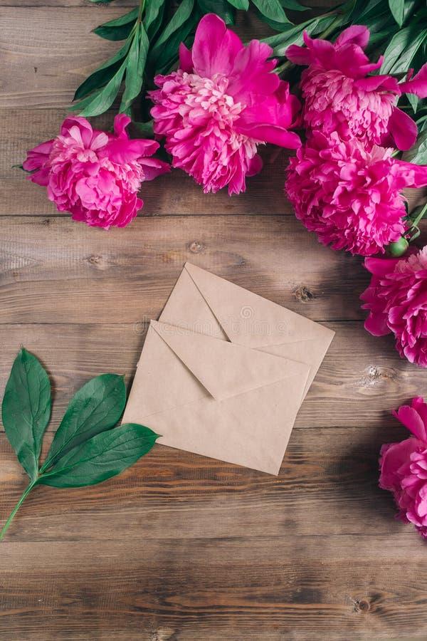 Reihe von Pfingstrosen und von Papierkarte und auf hölzernem Hintergrund mit Raum für Mitteilung Frauen ` s oder Mutter ` s Tages stockbild