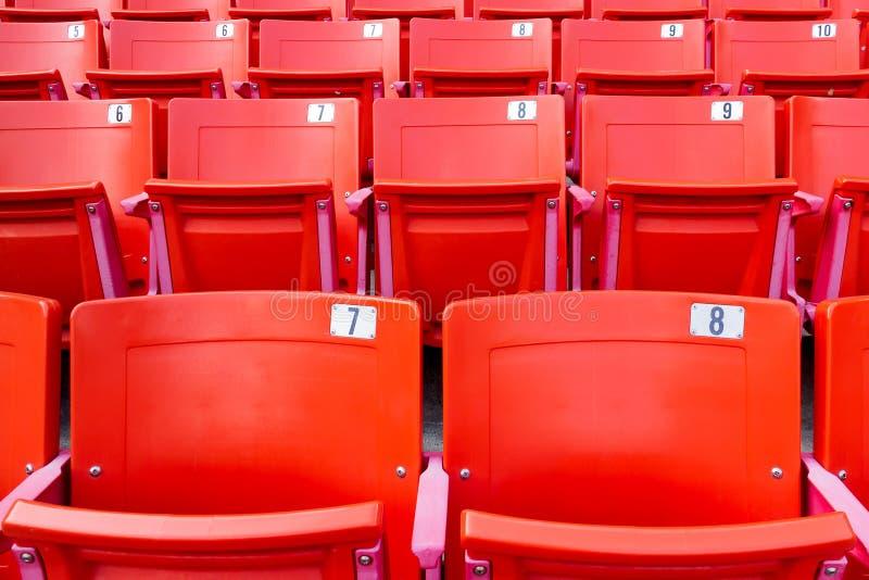 Reihe von roten Klappstühlen in einem Stadion stockbild