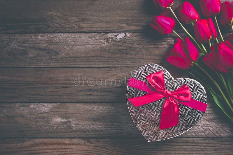 Reihe von roten Tulpen und von Kasten in Form Herzen auf h?lzernem Hintergrund stockbilder