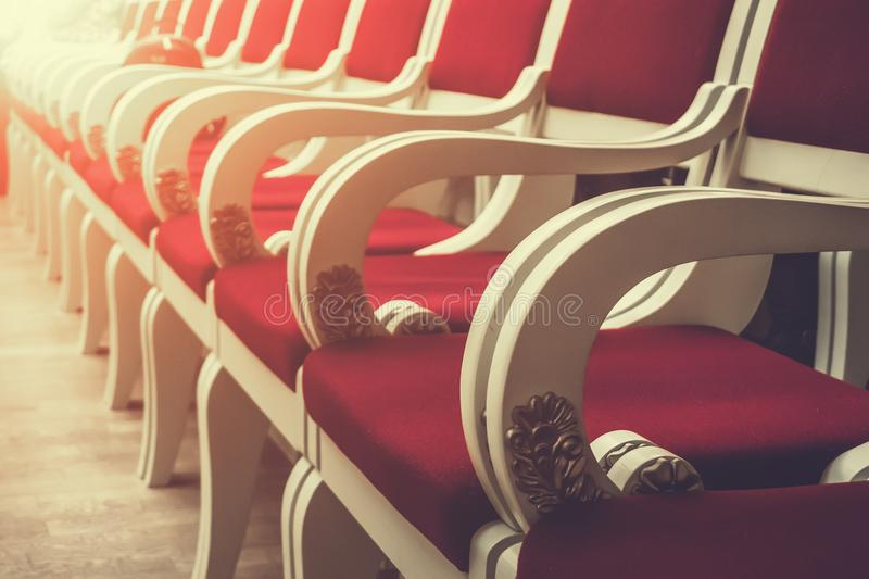 Reihe von roten Weinlesestühlen in der Oper oder Kino- oder Ereignishalle, Perspektive und selektiver Fokus lizenzfreie stockfotografie