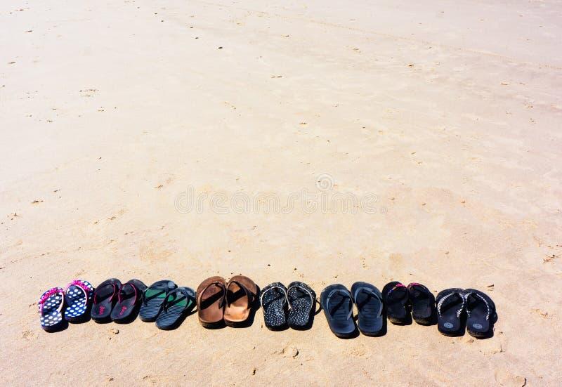 Reihe von Schuhen auf Strand-Hintergrund lizenzfreies stockbild