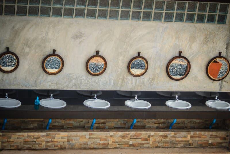 Reihe von Tünchebecken im Badezimmer mit Reihe von Spiegeln herein stockfotos