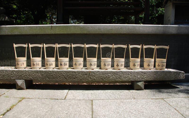 Reihe von Wasser-Eimern außerhalb des Schreins lizenzfreie stockfotos