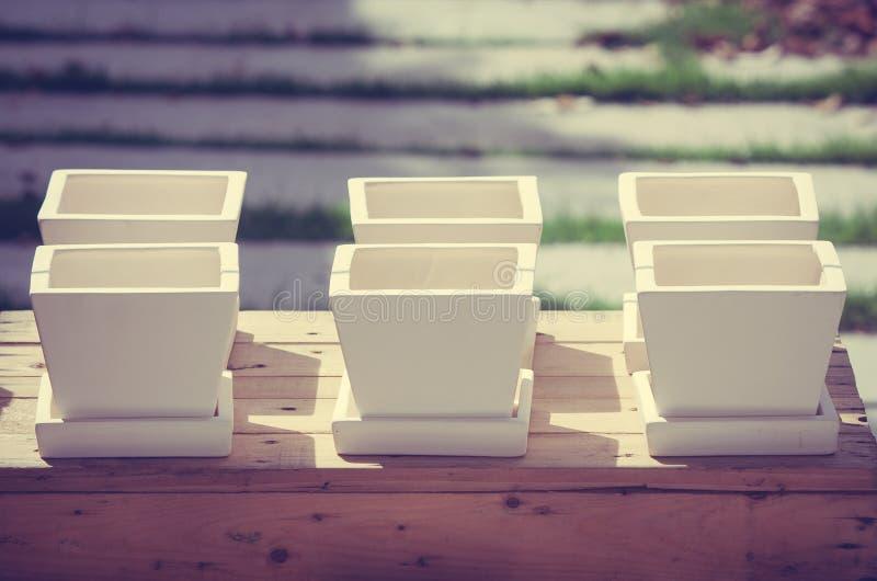 Reihe von weißen keramischen Blumentöpfen auf Holzkiste Garten am im Freien in der Weinleseart lizenzfreie stockfotos