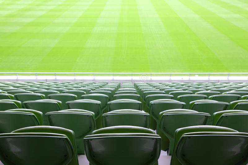 Reihen der gefalteten Plastiksitze im leeren Stadion stockfotografie