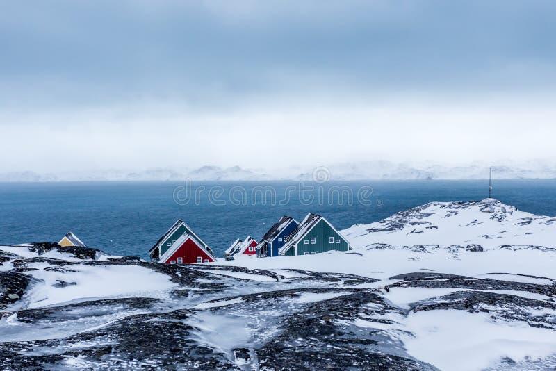 Reihen des bunten Inuit bringt das Verstecken in den Felsen mit Fjord herein unter lizenzfreie stockbilder