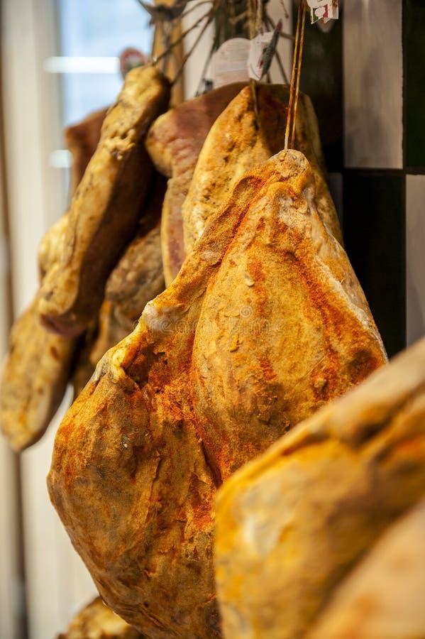 Reihen des getrockneten Italieners trockneten Schinken in Metzgerei stockfotografie