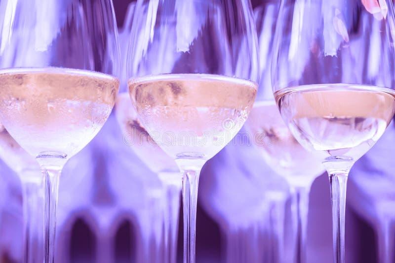 Reihen des kalten Weiß oder des rosafarbenen Weins im purpurroten Licht lizenzfreie stockbilder