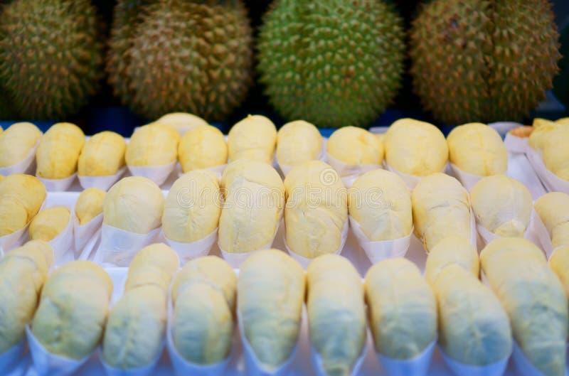 Reihen von abgezogenem gelbem Durain im Weißbuchverpacken und in einer Reihe des runden Durian mit brauner und grüner scharfer Ha stockfotos