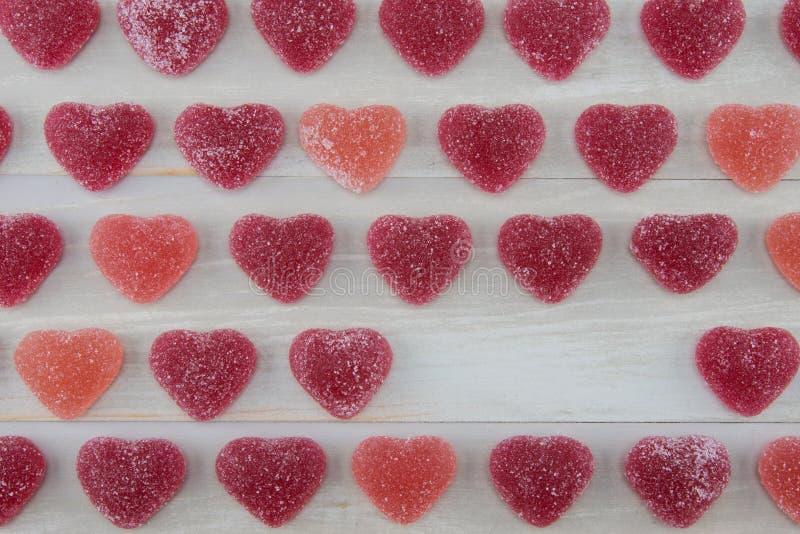 Reihen von dunkelroten und rosa gummiartigen Herzen mit leerem Raum lizenzfreies stockfoto