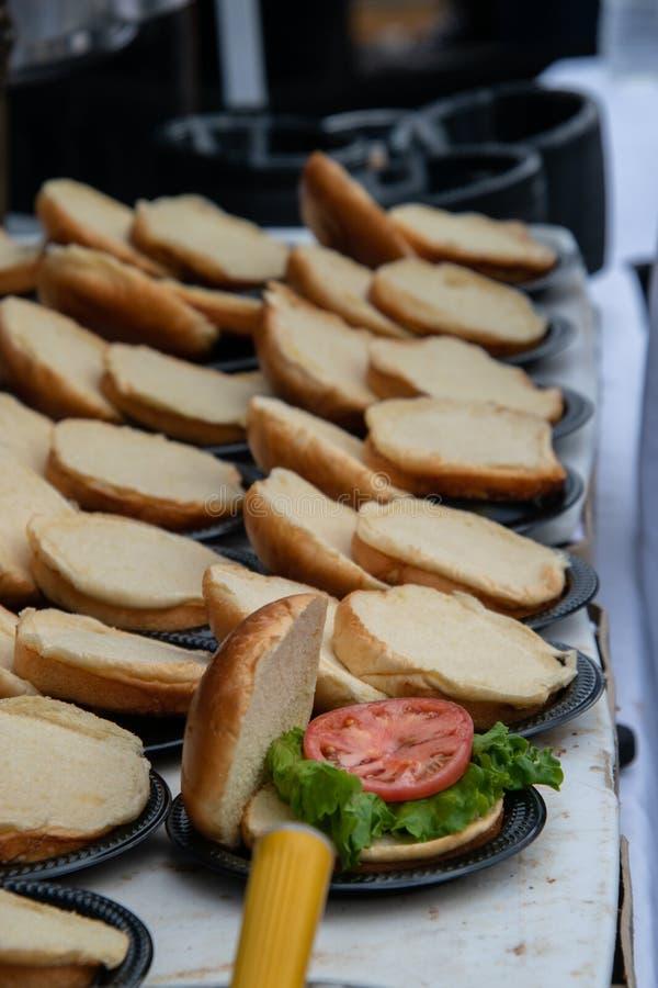 Reihen von geöffneten Hamburgerbrötchen auf einer Tabelle Nur man hatte Kopfsalat und eine Scheibe der Tomate auf ihm stockfotos