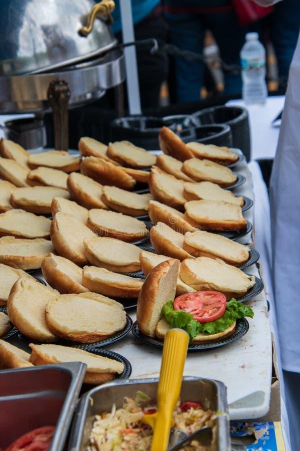 Reihen von geöffneten Hamburgerbrötchen auf einer Tabelle Nur man hatte Kopfsalat und eine Scheibe der Tomate auf ihm lizenzfreies stockfoto
