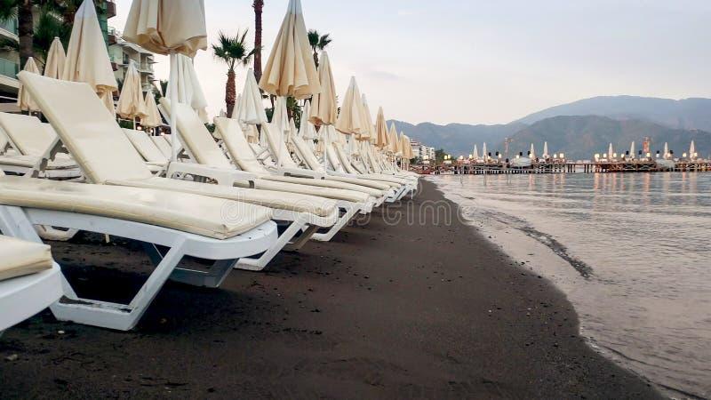 Reihen von leeren sunbeds und von Sonnenschirmen auf dem Seestrand bei Sonnenuntergang stockfotos