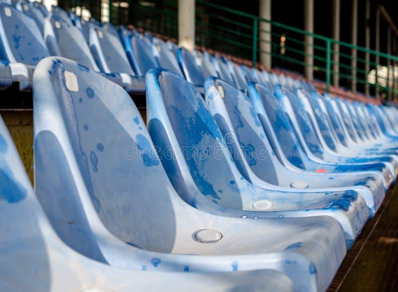 Reihen von nass blauen Plastiksitzen im Stadion stockfotos