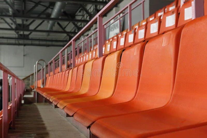 Reihen von orange Plastiksitzen auf modernem leerem Stadion lizenzfreie stockfotografie