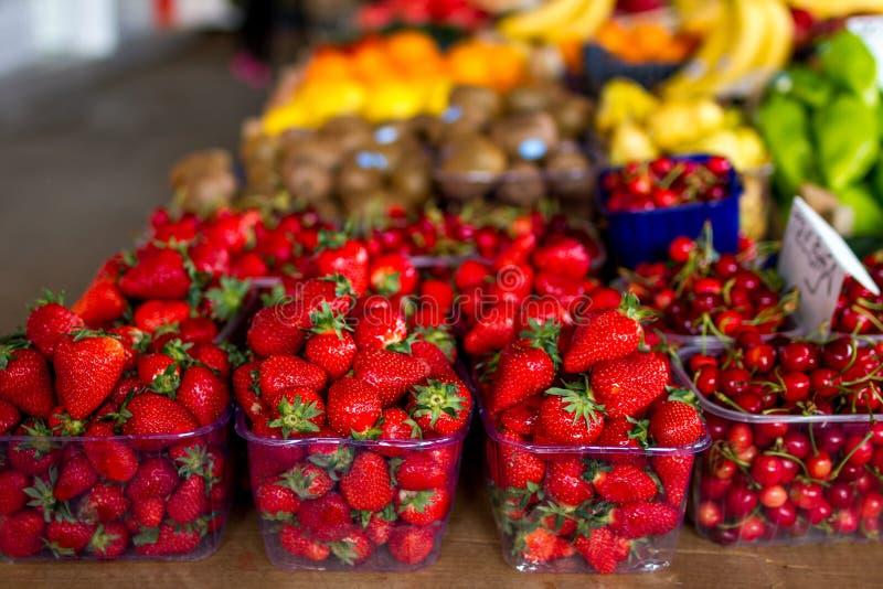 Reihen von süßen, roten Erdbeeren, mit anderen Früchten im Hintergrund lizenzfreie stockfotografie